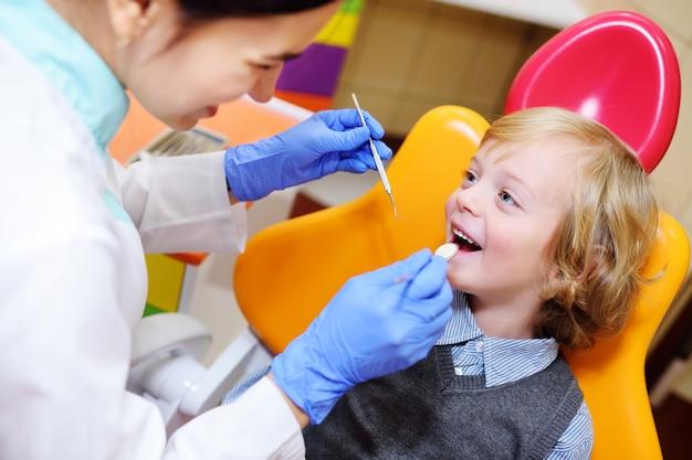 Criança sorridente com cabelo encaracolado claro no exame na cadeira odontológica