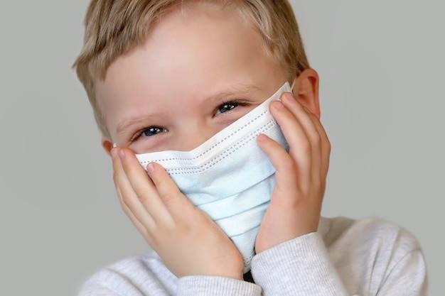 Criança sorridente com cabelo loiro na máscara médica. feliz para se proteger. plano de fundo cinza da moda.