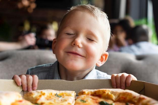 Criança sorridente com caixa de pizza