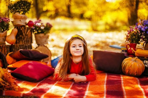 Criança sorridente com cesta de maçãs vermelhas, sentado no parque outono