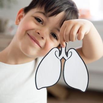 Criança sorridente com forma de pulmões