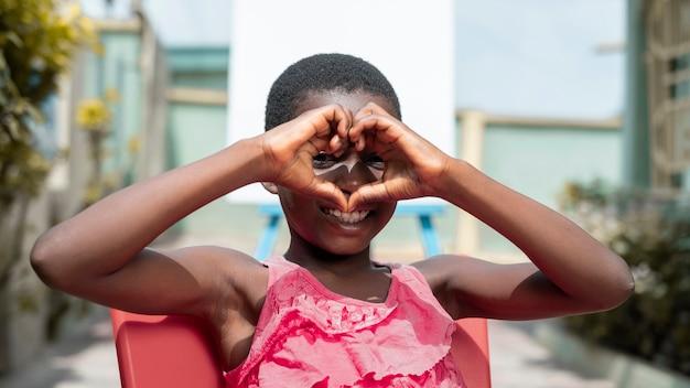 Criança sorridente com foto média ao ar livre