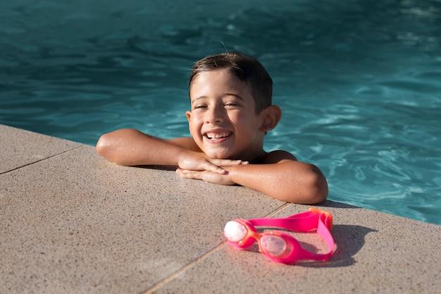 Criança sorridente com tiro médio na piscina