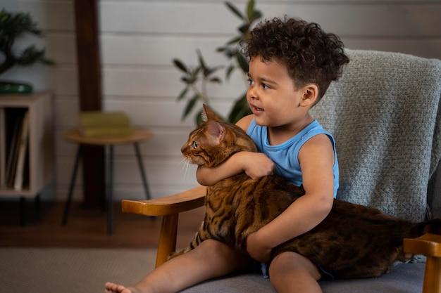 Criança sorridente com tiro médio segurando um gato