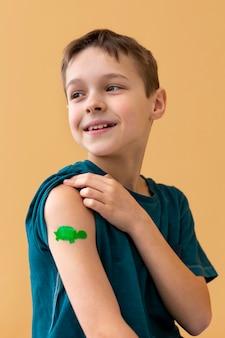 Criança sorridente com tiro médio usando band-aid