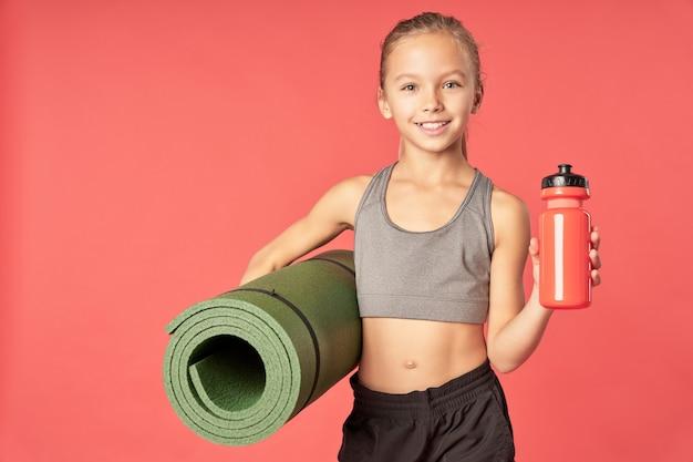Criança sorridente do sexo feminino segurando uma esteira rolada e uma bebida esportiva refrescante em pé contra um fundo vermelho