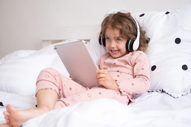 Criança sorridente e feliz menina caucasiana usando tablet em fones de ouvido sem fio na cama em casa
