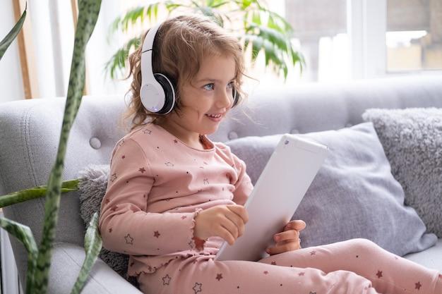 Criança sorridente e feliz menina caucasiana usando tablet em fones de ouvido sem fio no sofá em casa