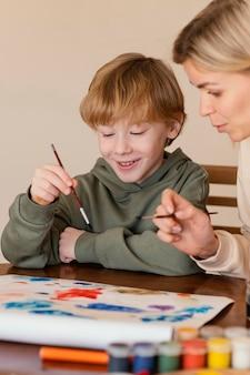 Criança sorridente em close-up pintando