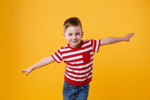 Criança sorridente em pé com as mãos espalhadas