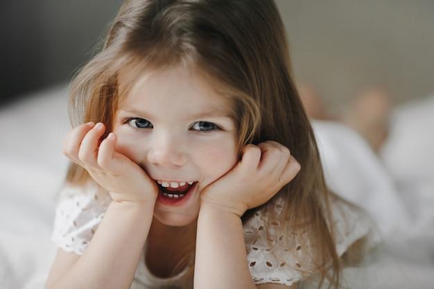 Criança sorridente feliz, deitada na cama