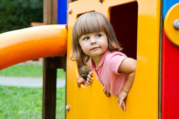 Criança sorridente feliz em pequena casa no parque infantil