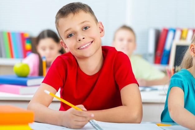 Criança sorridente na sala de aula, escrevendo, desenhando