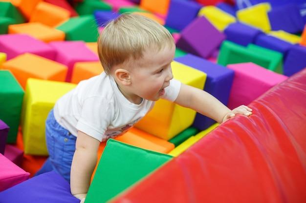 Criança sorridente na sala de jogos. menino engraçado em uma piscina com cubos de brinquedo macio colorido. descanso da família no centro infantil. criança no centro de entretenimento. garoto se divertir na sala de jogo. infância feliz
