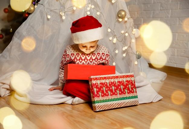 Criança sorridente olhando dentro de uma caixa de presente de natal brilhante ano novo
