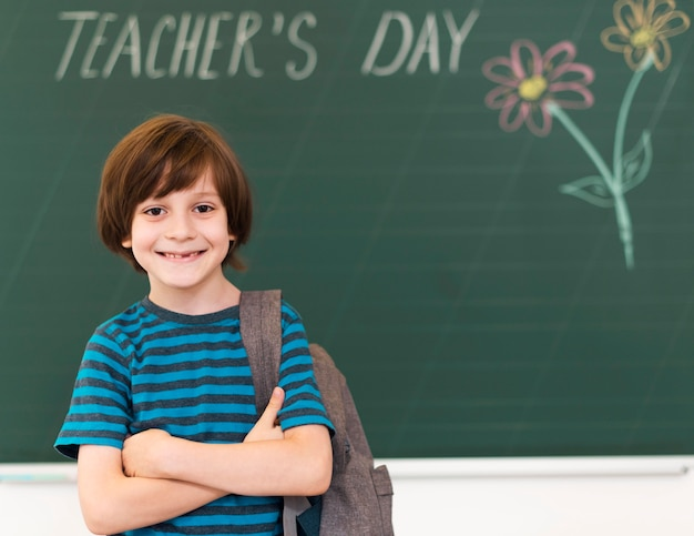 Criança sorridente posando ao lado do quadro-negro
