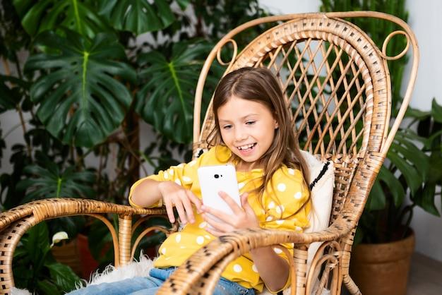 Criança sorridente se comunica on-line sentada na cadeira de balanço em casa