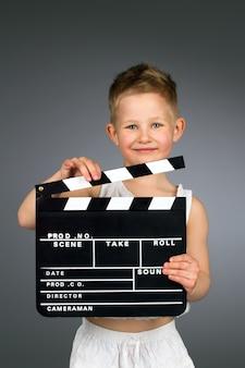 Criança sorridente segurando claquete de cinema.