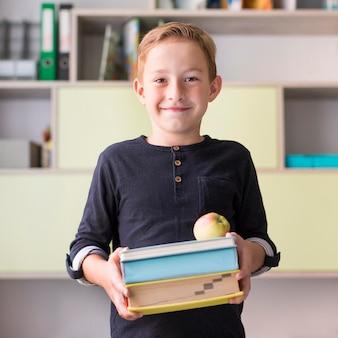 Criança sorridente segurando um monte de livros