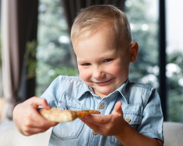 Criança sorridente segurando uma fatia de pizza