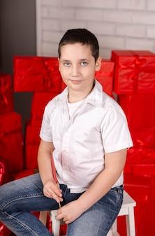 Criança sorridente, sentada em uma cadeira com caixas de presente vermelhas atrás
