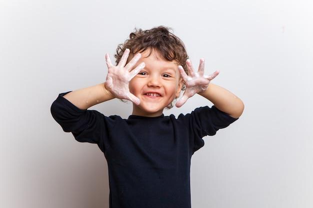 Criança sorridente, um menino em uma camiseta preta mostra as mãos na água e sabão em um estúdio branco.
