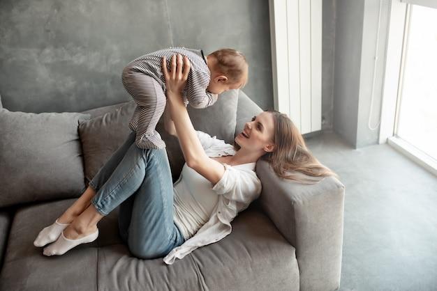 Criança sorrindo e feliz com a mãe no sofá