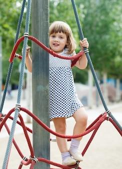 Criança sorrindo escalando nas cordas no campo de jogos