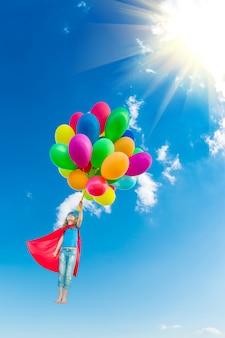 Criança super-herói brincando com balões multicoloridos brilhantes ao ar livre. criança se divertindo contra o céu azul