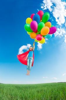 Criança super-herói brincando com balões multicoloridos brilhantes ao ar livre. criança se divertindo no campo verde primavera