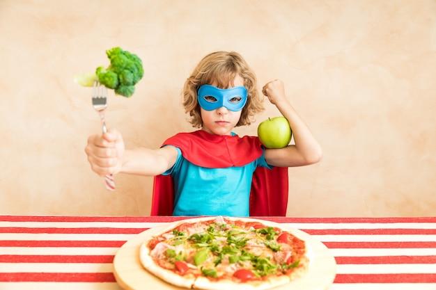 Criança super-herói comendo superalimento