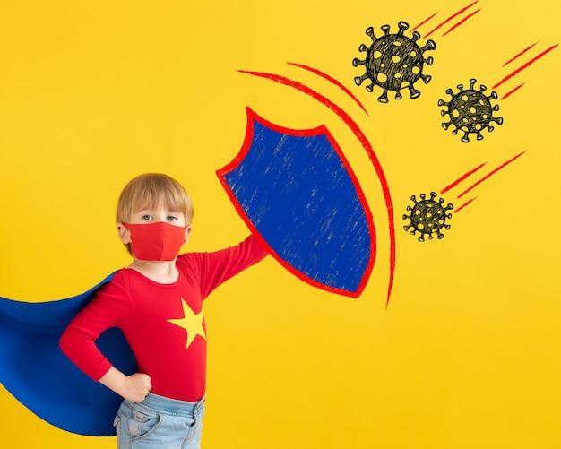 Criança super-herói usando máscara protetora interna