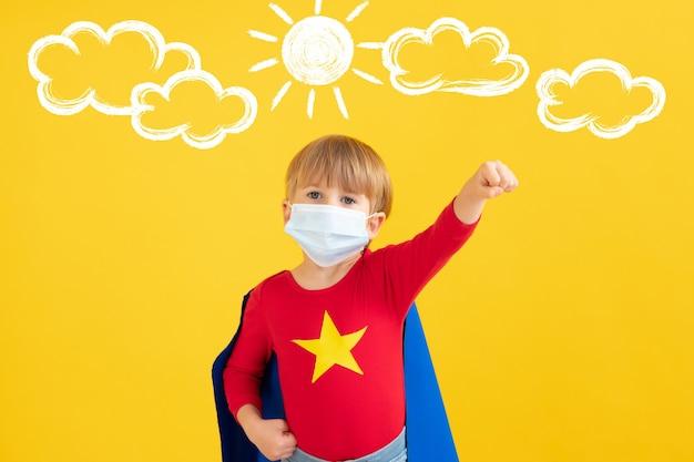 Criança super-herói usando máscara protetora