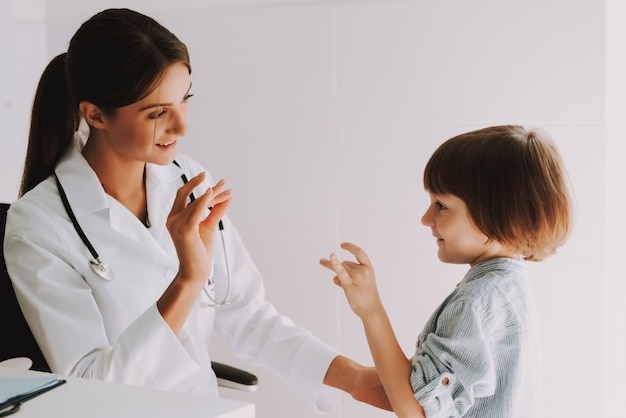 Criança surda fala linguagem gestual com pediatra.