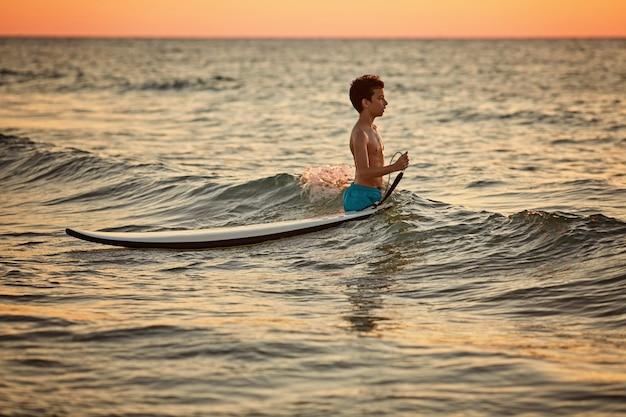 Criança surfando na praia tropical