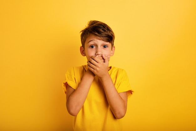 Criança surpreendida quer falar. expressão espantada e admirada. fundo amarelo
