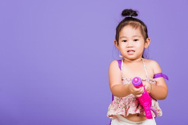 Criança tailandesa engraçada segurando a pistola d'água de brinquedo e sorrindo para o festival songkran
