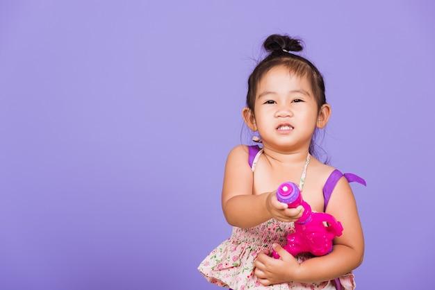 Criança tailandesa engraçada segurando pistola de água de brinquedo e sorriso, festival songkran da tailândia