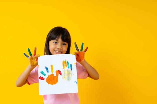 Criança tailandesa mostra papel de pintura em amarelo