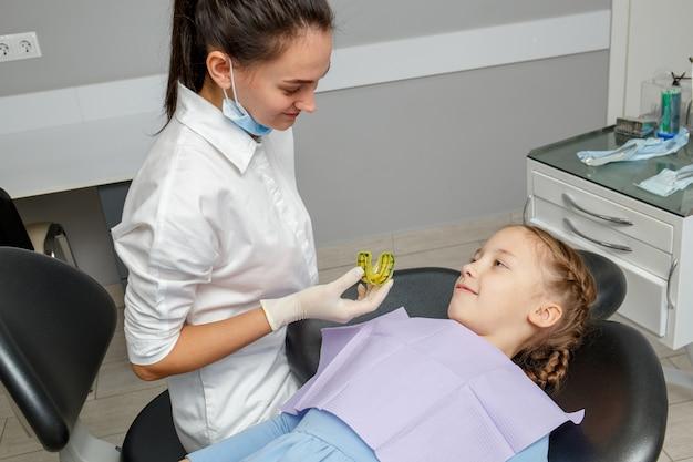 Criança tendo uma consulta ortodontista no consultório do dentista