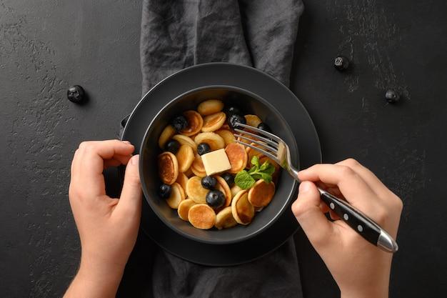 Criança tenta pequenas panquecas de cereais com mirtilos em preto