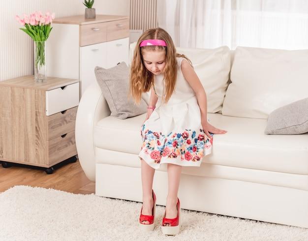 Criança tentando novos sapatos de salto