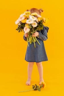 Criança tímida, segurando o buquê de flores