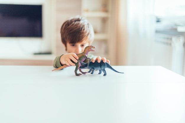 Criança, tocando, com, brinquedo, dinossauros