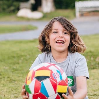 Criança, tocando, com, um, futebol