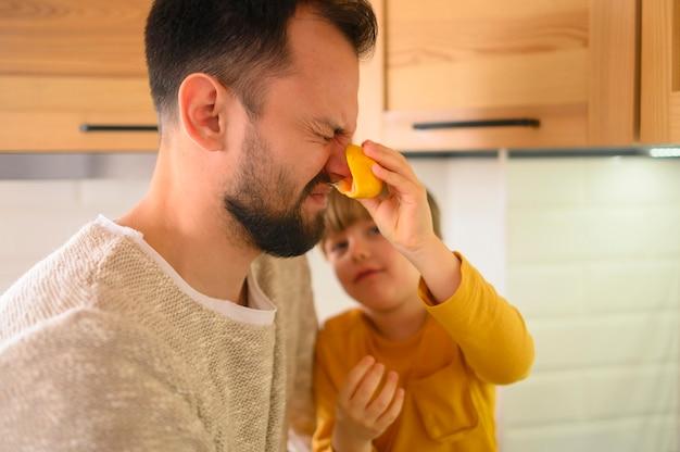 Criança tocando o nariz do pai com uma laranja