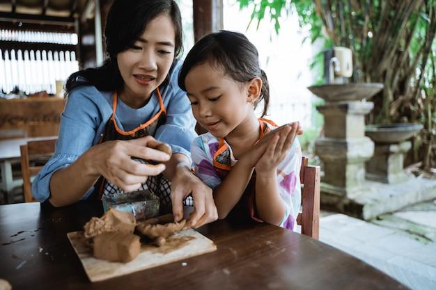 Criança trabalhando com argila fazendo cerâmica