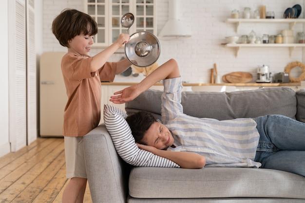 Criança travessa resmungando utensílios de cozinha enquanto mãe estressada e cansada dormindo no sofá da sala