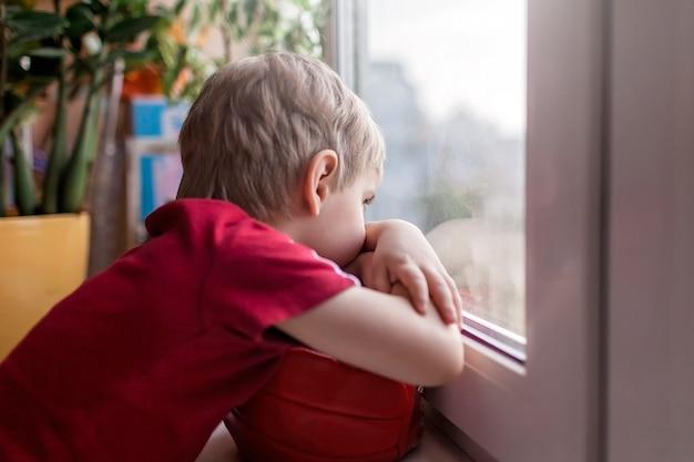 Criança triste bonitinha sentada no peitoril da janela e olhando para a rua