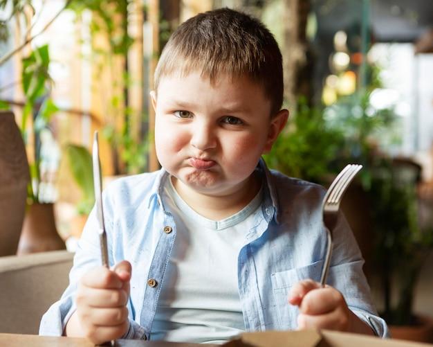 Criança triste com tiro médio com talheres